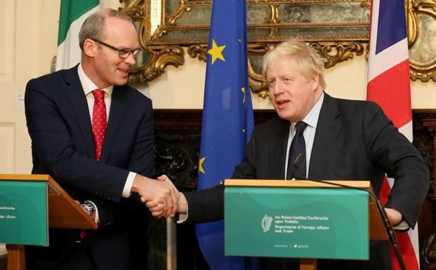 Coveney (i) esstrecha la mano de Boris Johnson. /Paul FAITH (Afp)