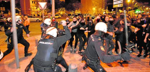 Agentes de la Policía Nacional desplegados en el Hotel Nelva cargan contra los jóvenes que se manifestaban en la puerta. agm/ VICENTE VICÉNS /