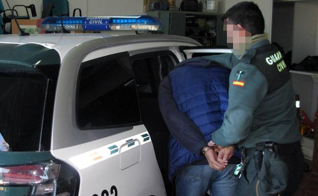 Un guardia civil esposa a uno de los detenidos./Guardia Civil