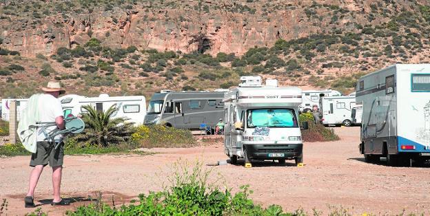 Un grupo de autocaravanas aparcadas en un solar privado, frente a la playa de La Chapineta, en La Azohía. / ANTONIO GIL / AGM