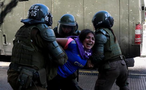 La Policía deteniene a uno de los manifestantes.