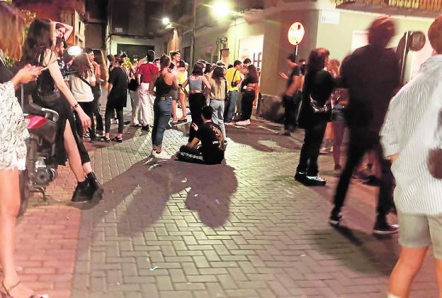 Grupos de jóvenes se concentran en la entrada de un bar en una de las esquinas del barrio de Santa Eulalia.